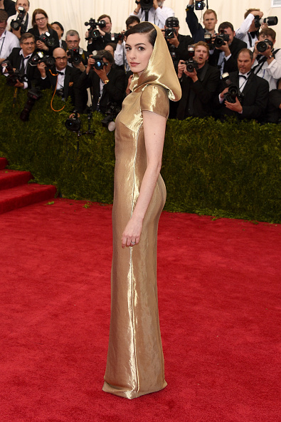 Anne Hathaway in a hooded golden gown from the Ralph Lauren Collection and Repossi jewelry.
