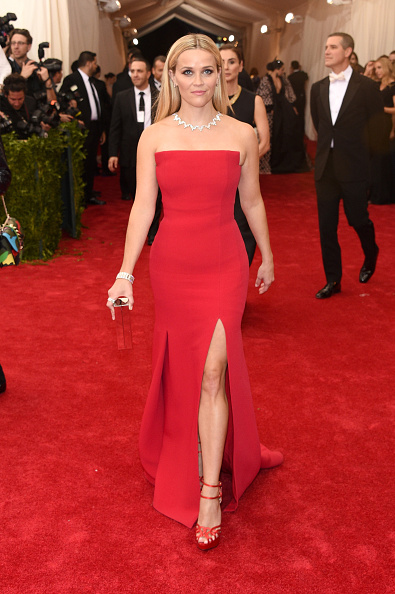 Reese Witherspoon is showing some leg in a Jason Wu red dress, Charlotte Olympia heels, and Tiffany & Co jewels.
