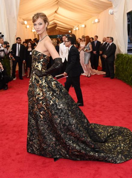 Model Karlie Kloss chose a strapless brocade gown by Oscar de la Renta.